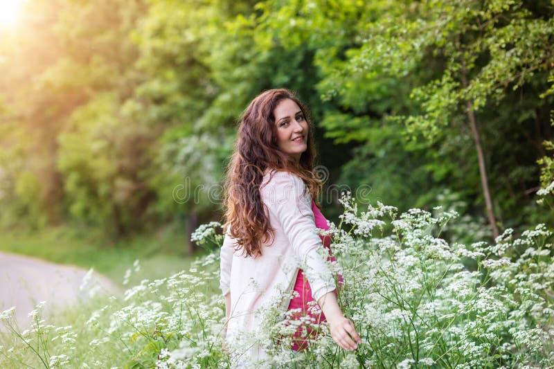 Mooie zwangere vrouwen die haar buik houden De aard van de zomer royalty-vrije stock foto