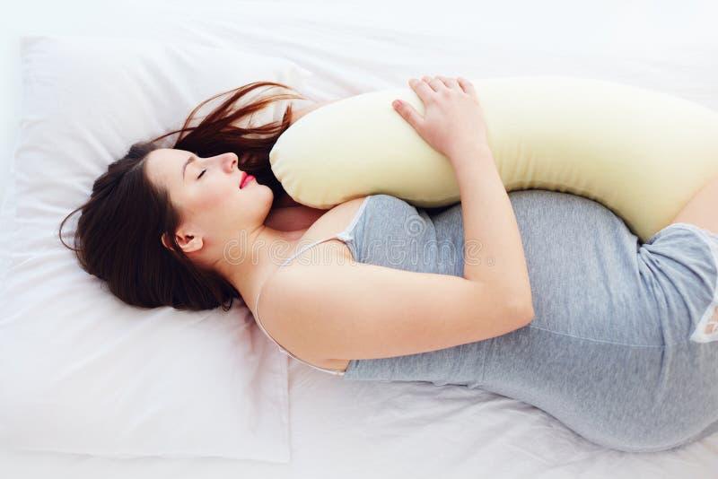 Mooie zwangere vrouwenslaap comfortabel met buik ondersteunend hoofdkussen royalty-vrije stock fotografie
