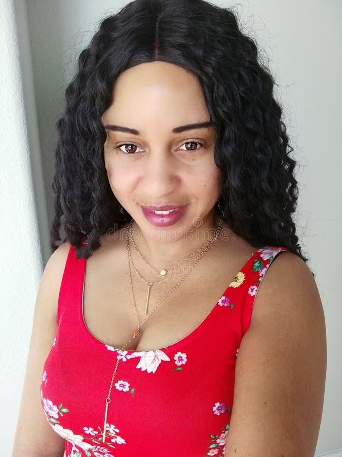 Mooie Zwarte Krullende Haarvrouw in het Rode Bloemenkleding Denken royalty-vrije stock foto's