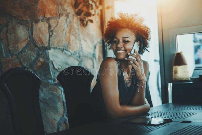 Mooie zwarte krullende vrouw die in donkere bureauruimte wachten royalty-vrije stock afbeeldingen