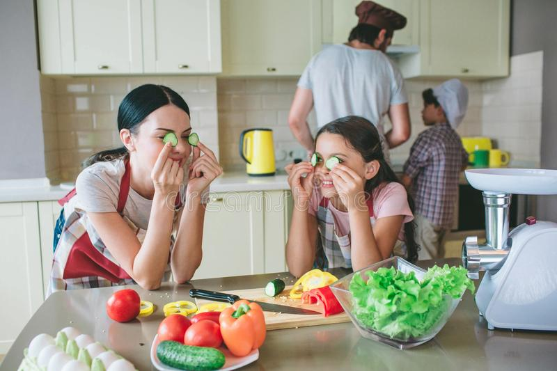 Moom和一起女儿立场和倾斜在桌上 他们使用与黄瓜圆的片断  他们投入了它  库存照片