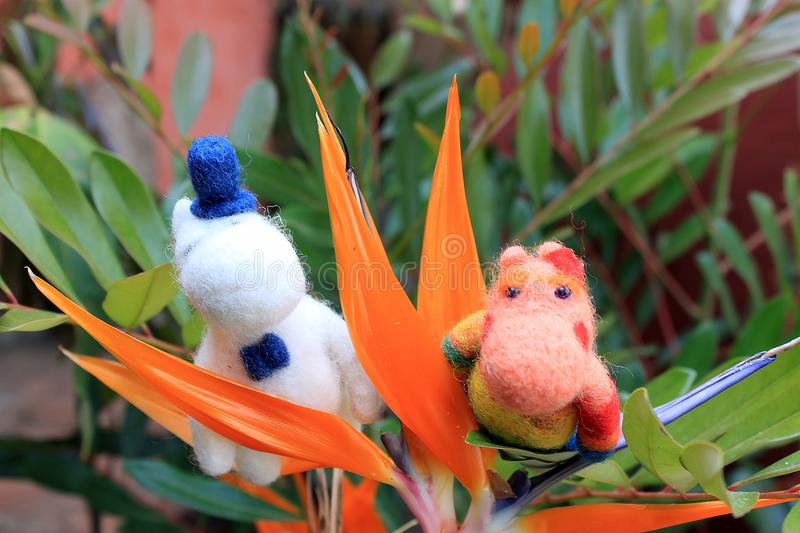 Two trolls in the tropical flower in mexican garden. Moomin troll couple on the tropical flower in Mexico, romantic trolls with flowers, felted toy royalty free stock image