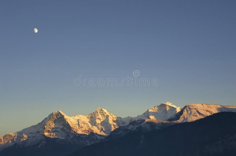 Moon above the Jungfrau mountain range (Switzerland) royalty free stock images