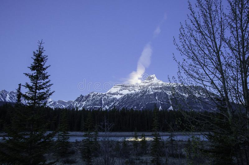 Moon above Rocky Mountains along beautiful blue river stock images