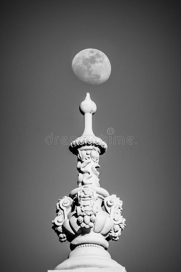 Moon balances over a finial decorating one of the buildings in Balboa Park in San Diego, California. Moon balances over one of the decorative finials in Balboa royalty free stock photo