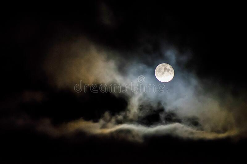 Moon behind clouds stock image