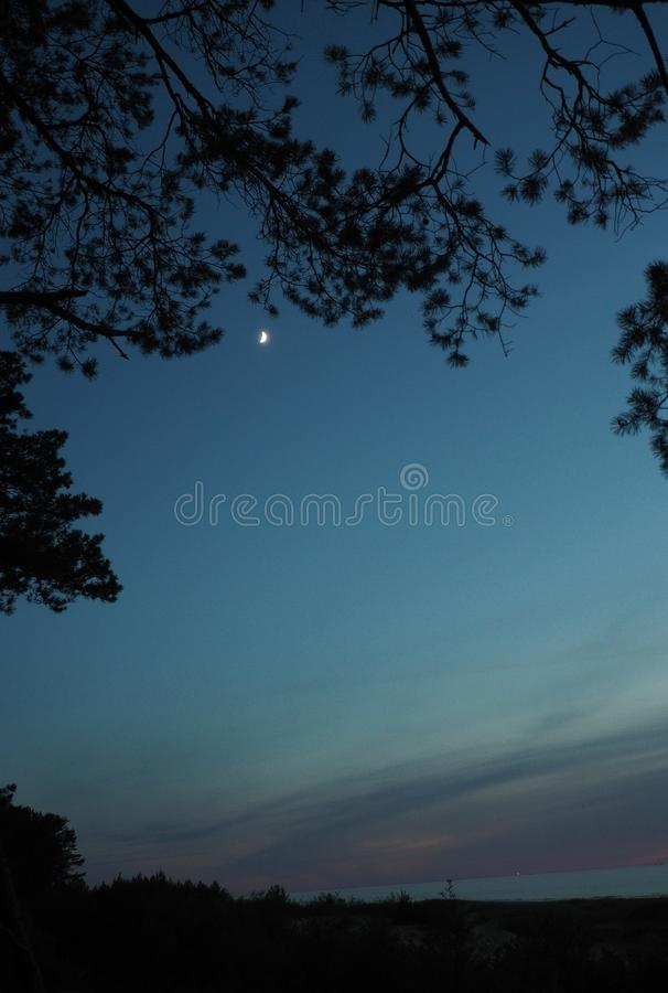 Moon on blue sky after sunset. Moon observing on blue and sky over Baltic sea after sunset stock images