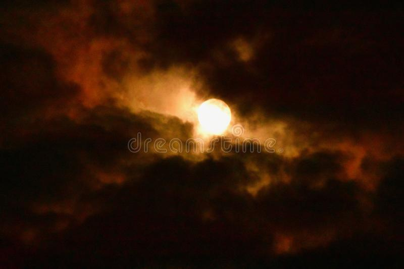 The moon brightens the dark clouds. The full moon breaks through the night clouds giving a golden glow through the black clouds royalty free stock images