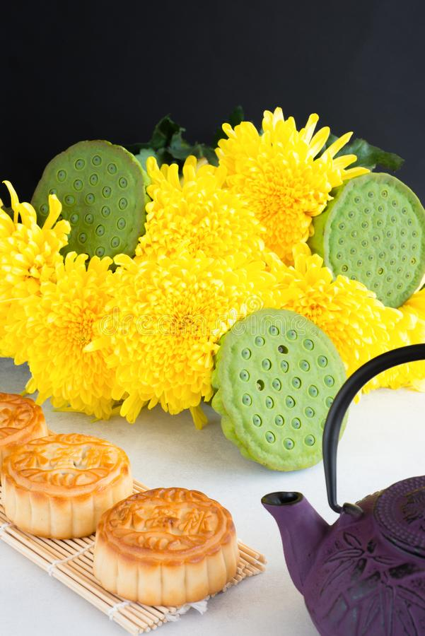 Mooncakes, teapot, chrysanthemum flowers, lotus seeds in pods on white background. Chinese mid-autumn festival food. stock image