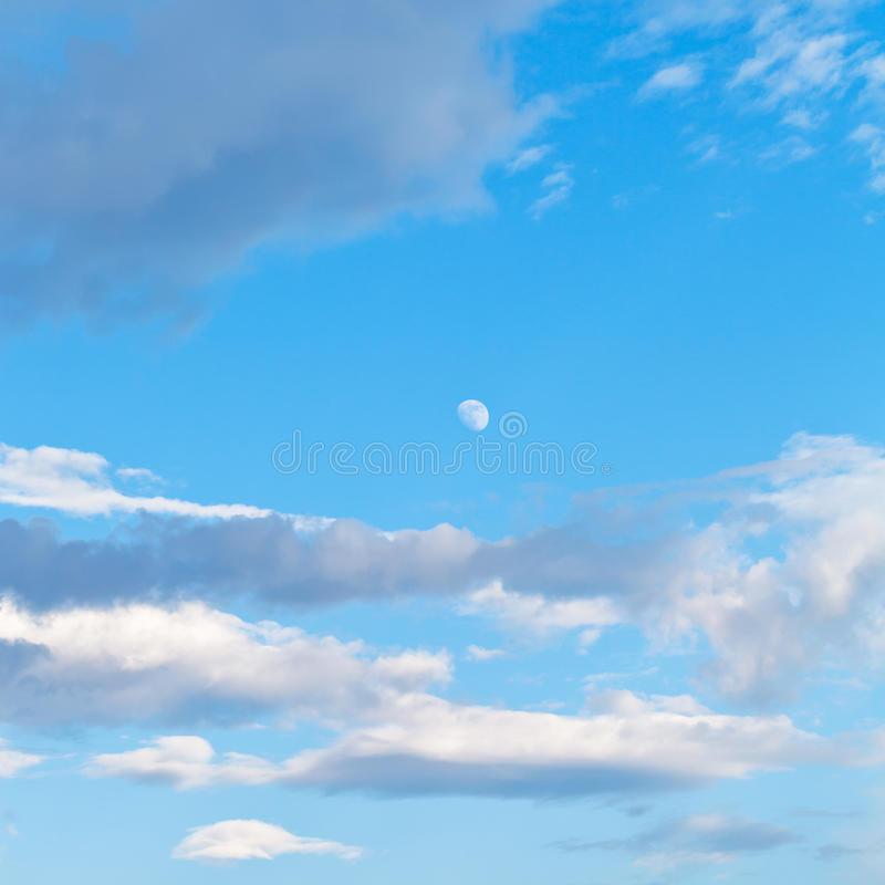 Moon and clouds in blue evening sky royalty free stock photo