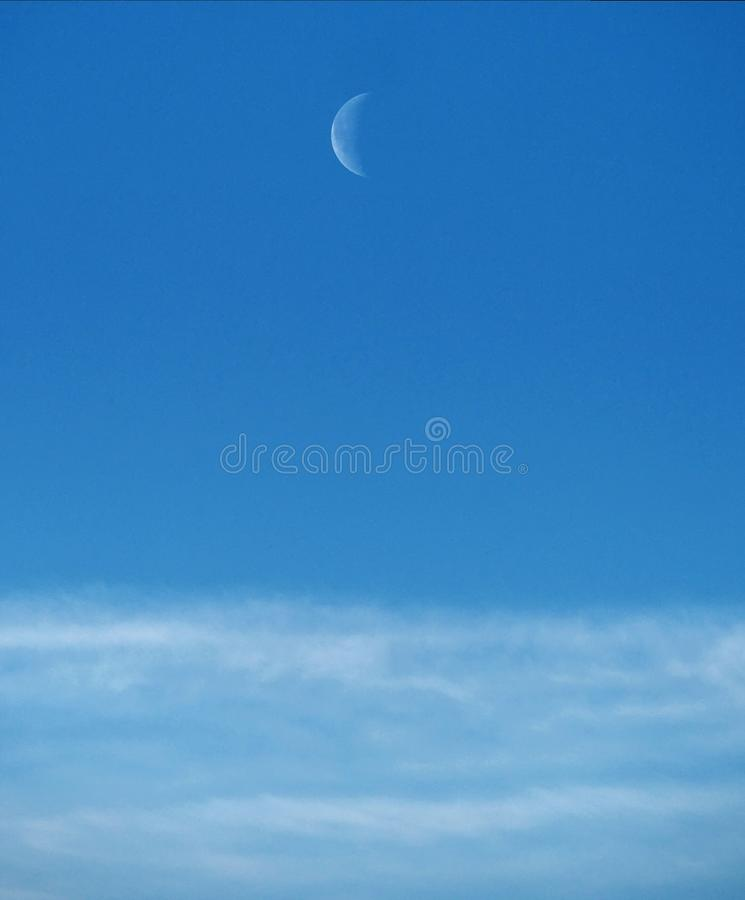 Moon and clouds observing on blue ksy stock image