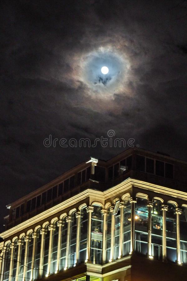 Moon and clouds observing over city royalty free stock image