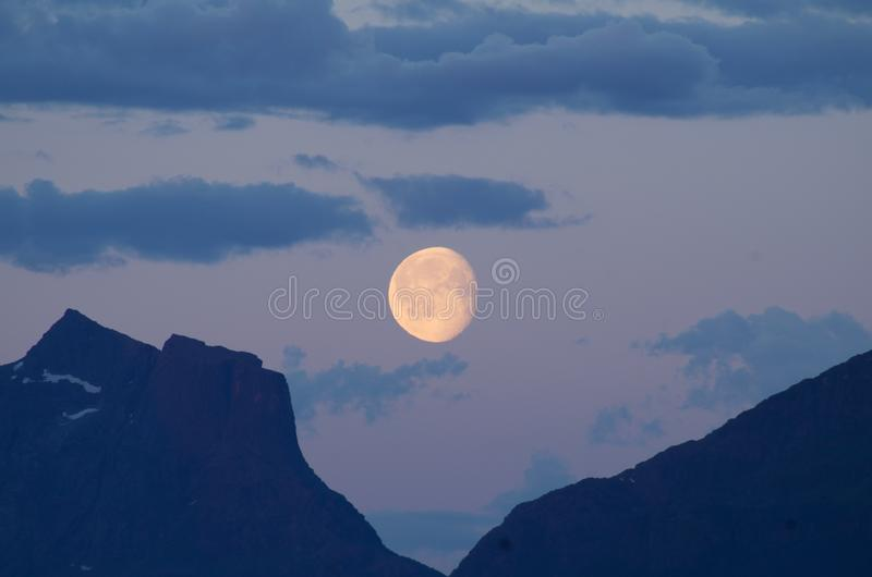 Moon in cloudy sky in between mountains stock photography
