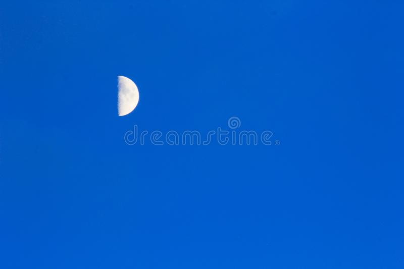 Moon crescent close-up on blue sky as background. Postcard royalty free stock image