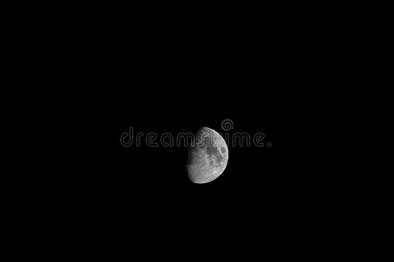 Moon in dark sky, terminator and craters on the bright surface royalty free stock images