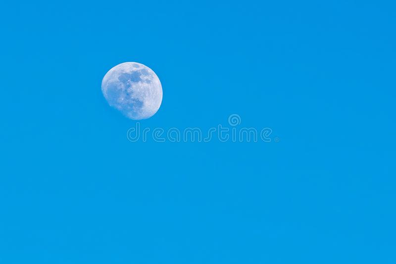 Moon during the day, against a flawless beautiful blue sky, close-up. Moon during the day, against a flawless and beautiful blue sky, close-up stock photos