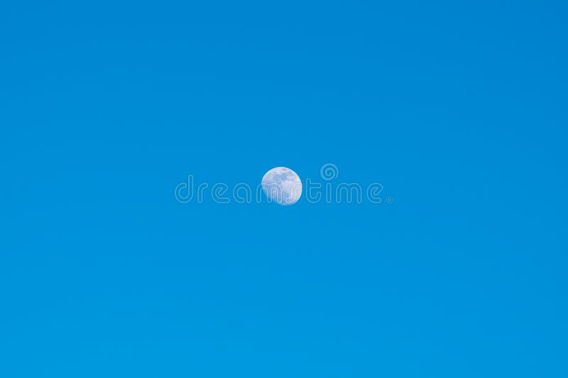 Moon during the day, against a flawless beautiful blue sky, close-up. Moon during the day, against a flawless and beautiful blue sky, close-up stock images