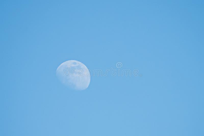 Moon in daylight sky stock images