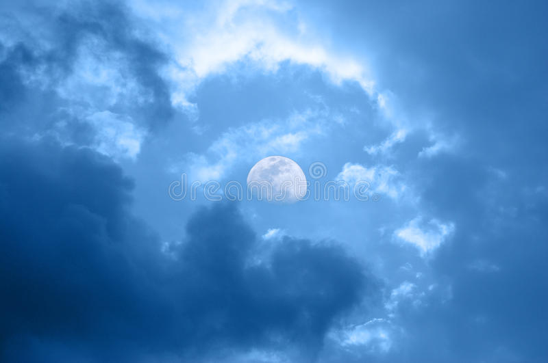 Moon in daytime on blue sky. With cumulus cloud royalty free stock image