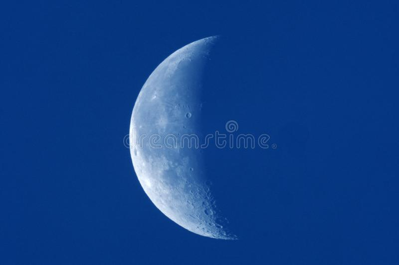 Moon details observing on day blue sky stock image