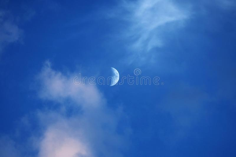 Moon and clouds on blue sky royalty free stock image