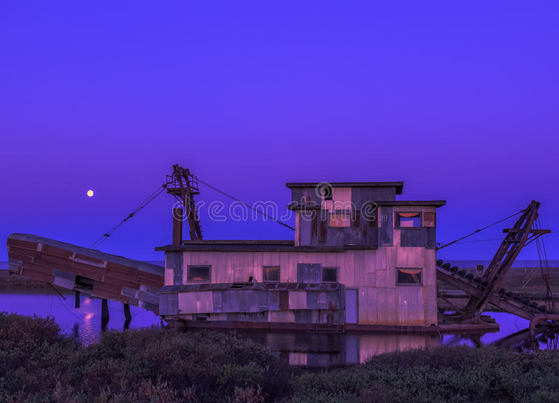 Moon And The Dredge. An Alaskan gold dredge receiving warm accommodations from the setting sun as well as the rising moon royalty free stock photo