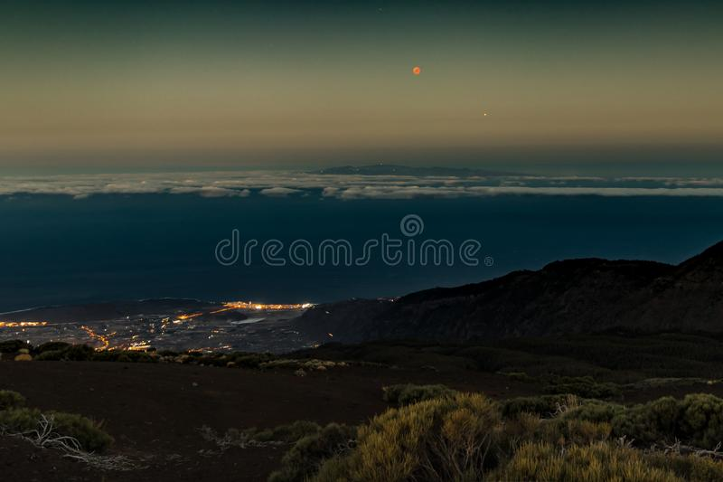Moon eclipse July 27, 2018, Tenerife. Red Moon and Mars close to each other just after sunset. Night lights of seashore. stock image