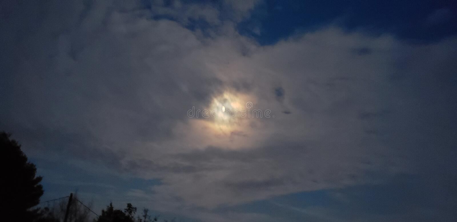 Moon. Evening moon begins the night behind the clouds royalty free stock image