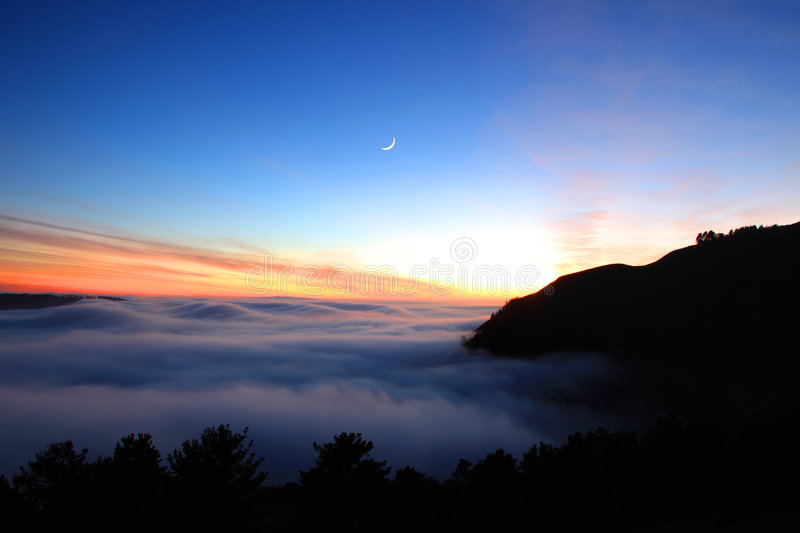 Moon and fog after sunset. The famous bay area fog and moon after sunset near golden gate bridge royalty free stock photo