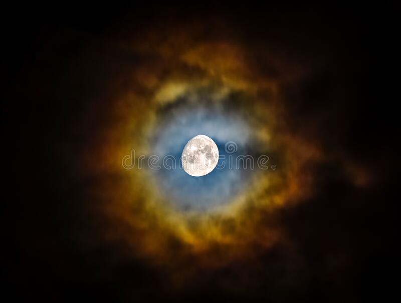 Moon, almost full, shining through clouds creating a vibrant and colorful halo. Natural phenomenon. Beautiful and scenic skyscape. Scenic cloudscape at night stock photography