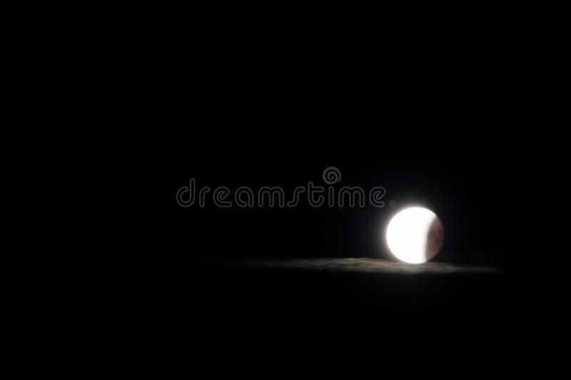 Moon and glowing cloud. In the night during last phase of total lunar eclipse stock photography