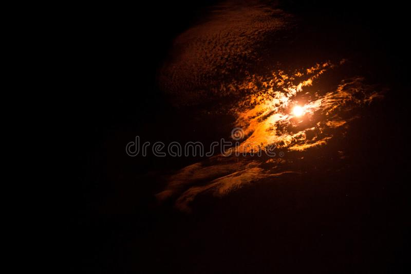 Moon glowing thru epic clouds on a black sky stock images