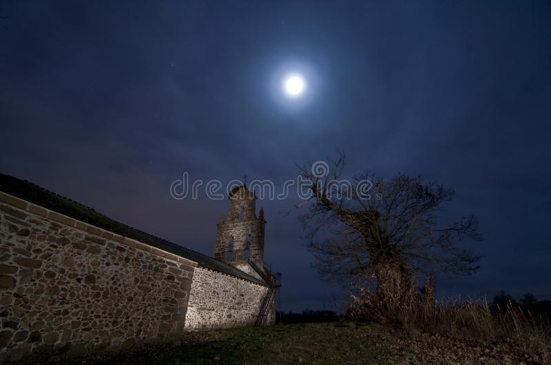 Moon halo atmospheric phenomenon with old church and tree. Moon halo is an atmospheric phenomenon that creates an halo around the moon royalty free stock photography