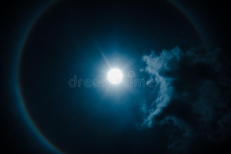 Moon halo phenomenon. Nighttime sky and bright full moon with sh. Moon halo phenomenon. Beautiful night landscape of dark blue sky and bright ring around the royalty free stock photography