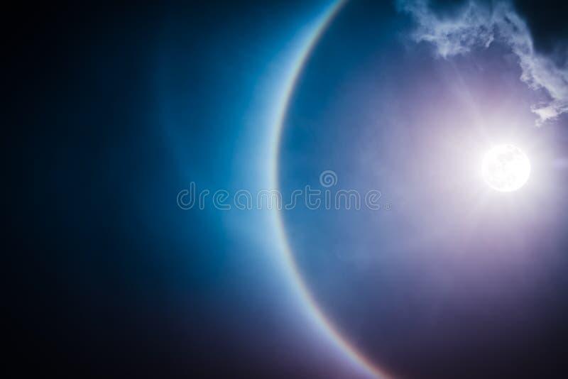 Moon halo phenomenon. Nighttime sky and bright full moon with sh. Moon halo phenomenon. Beautiful night landscape of dark sky and bright ring around the moon stock photo