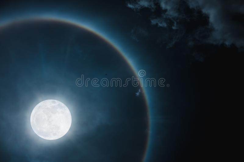 Moon halo phenomenon. Nighttime sky and bright full moon with sh. Moon halo phenomenon. Beautiful night landscape of dark sky and bright ring around the moon royalty free stock images