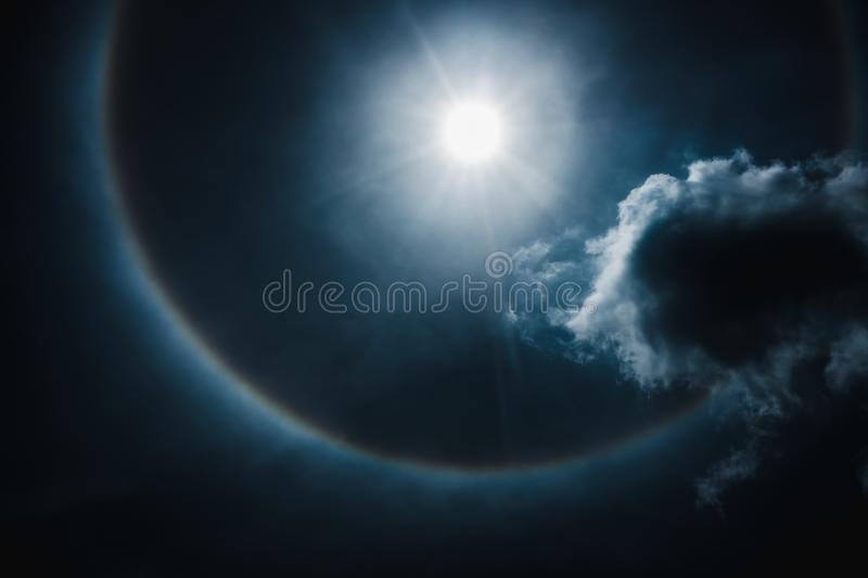 Moon halo phenomenon. Nighttime sky and bright full moon with sh. Moon halo phenomenon. Beautiful night landscape of dark blue sky and bright ring around the royalty free stock photo