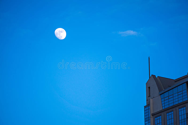 Moon hovering over high rise building in the city stock image