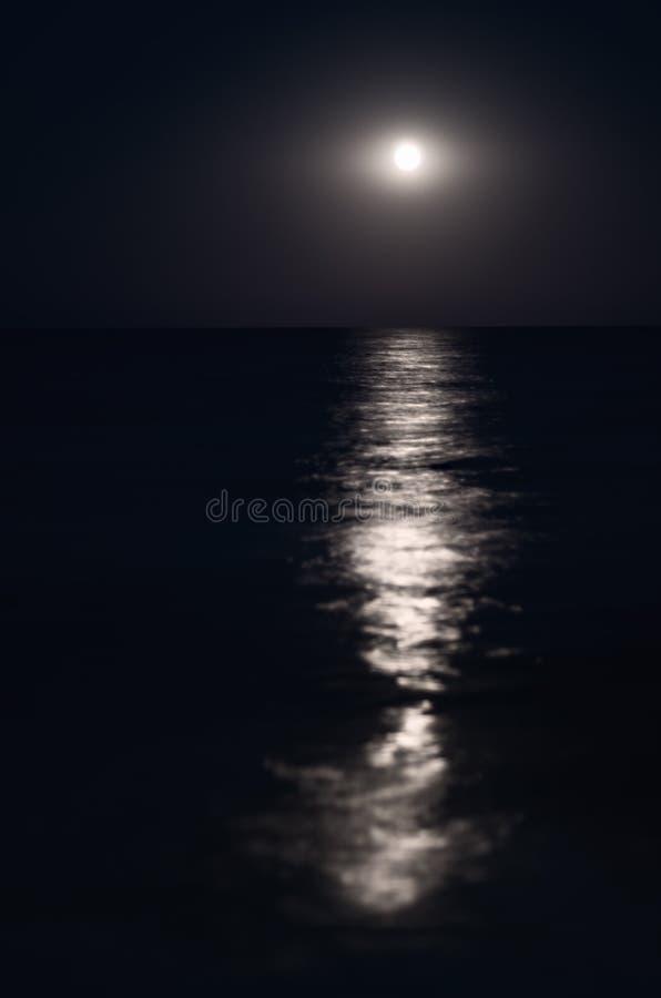 Moon im Nachtblauen Himmel, Seehorizont, Wellen, Reflexion des Lichtes stockfoto