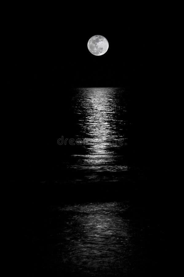 Moon inställningen på havet. arkivfoto