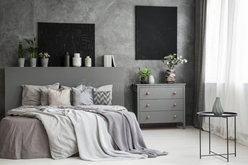 Moon la tela su una parete grigia in una camera da letto accogliente monocromatica inter immagini stock