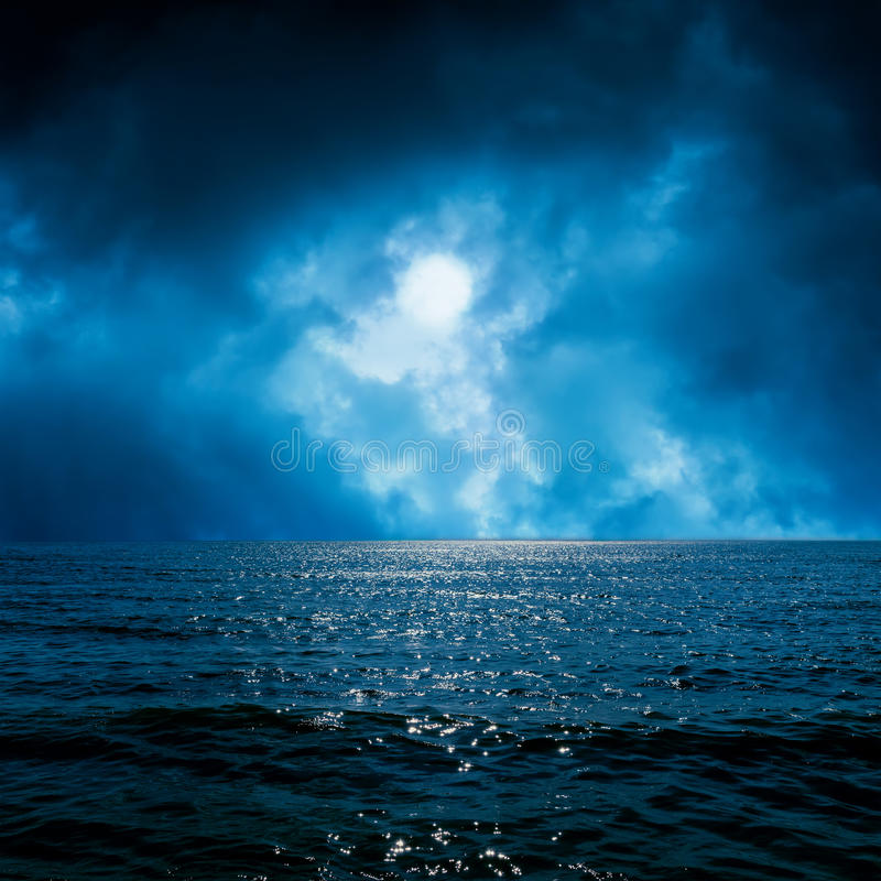 Moon light in dramatic sky over sea royalty free stock photos