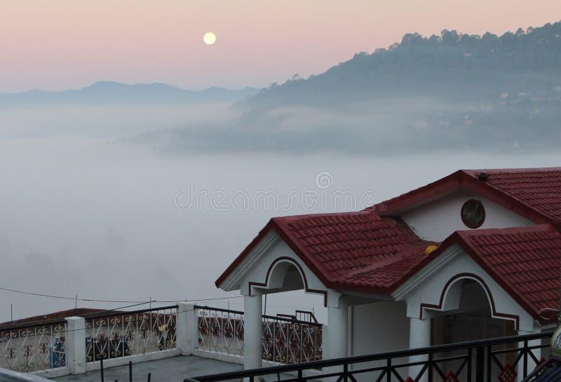 Moon met rode hemel en mist van huis royalty-vrije stock fotografie