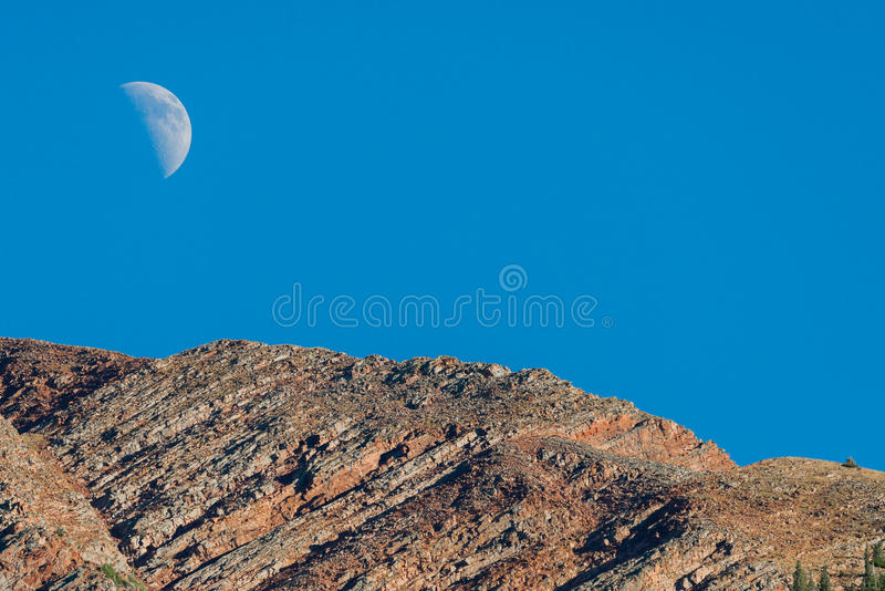 Moon and mountain summit peak. The moon seen rising above a mountain peak summit - colorado nature landscape photography royalty free stock photos