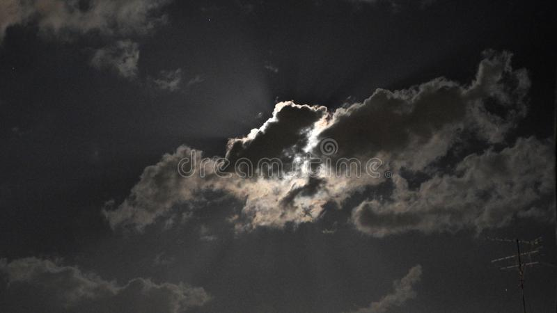 Moon. Mysterious. Mysterious. Lurking behind the clouds. Illuminating the coming rain. Alarming. Awesome. And at the same time - b. Eautiful royalty free stock images