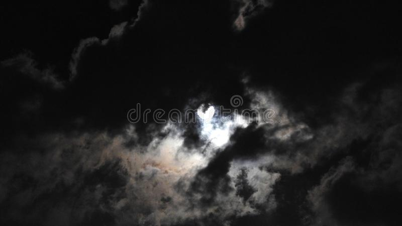 Moon. Mysterious. Mysterious. Lurking behind the clouds. Illuminating the coming rain. Alarming. Awesome. And at the same time - b. Eautiful royalty free stock photography