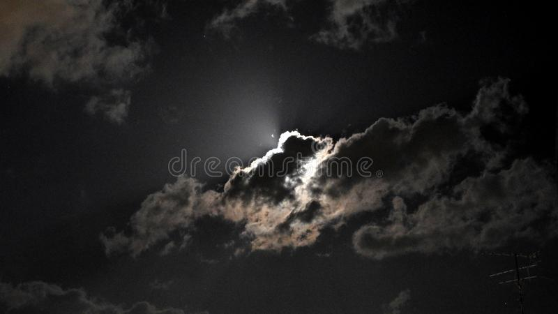 Moon. Mysterious. Mysterious. Lurking behind the clouds. Illuminating the coming rain. Alarming. Awesome. And at the same time - b. Eautiful stock photo