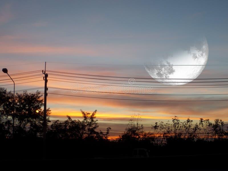 moon na nuvem escura do céu do por do sol e na linha elétrica do poder da silhueta imagens de stock