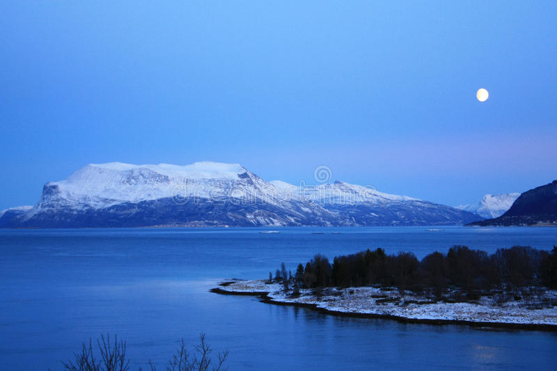 Moon on Narvik's fjord. Fjord of Narvik's region enlighted by the moon at 1.30 PM in the winter's dark period royalty free stock photos