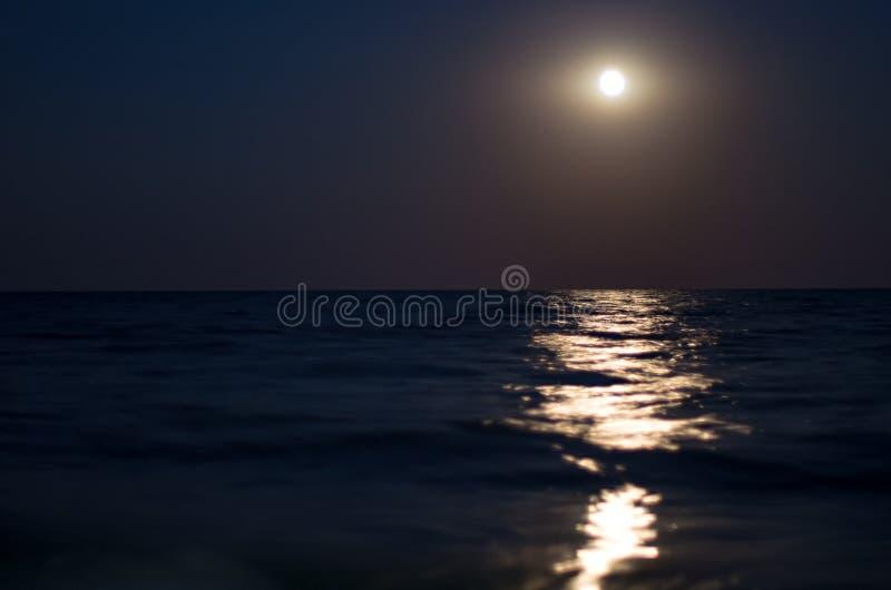 Moon nel cielo notturno, l'orizzonte di mare, onde fotografia stock